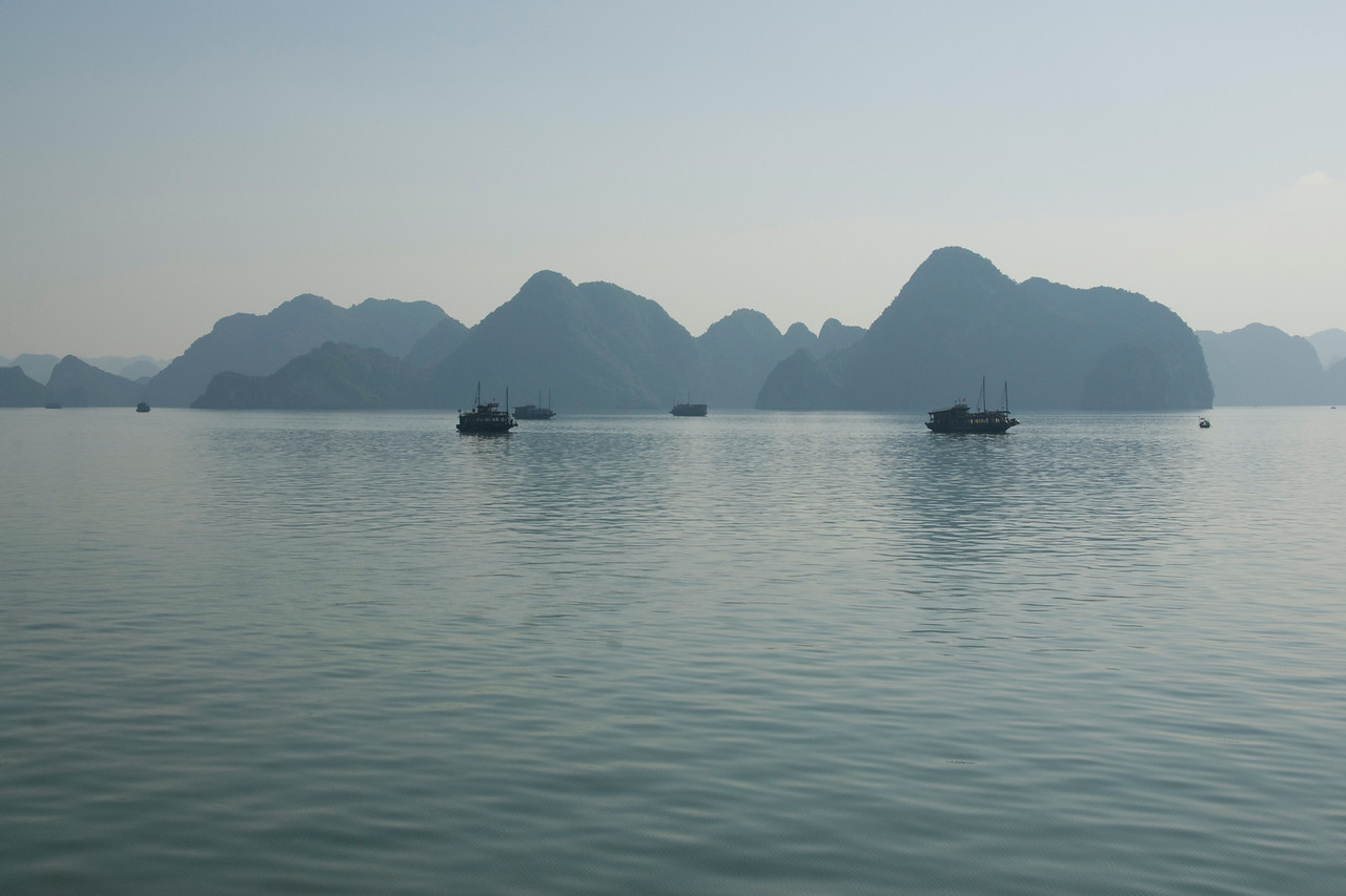 Boats against silhouette of islands - Ha Long Bay, Vietnam