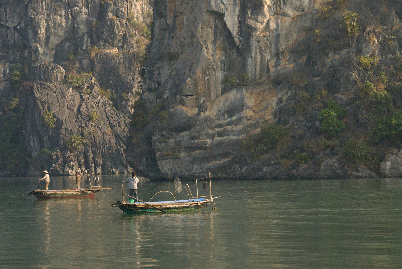 Two fishermen standing on their boats - Ha Long Bay, Vietnam