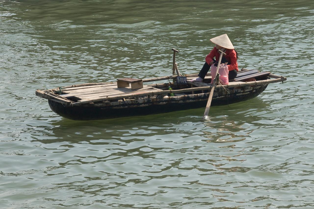 Woman sits on a row boat - Ha Long Bay, Vietnam