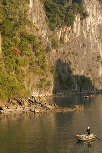 Solitary boat against steep rock cliffs - Ha Long Bay, Vietnam