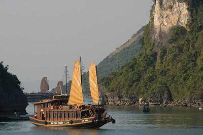 Tourist boat cruising next to islands in Ha Long Bay, Vietnam