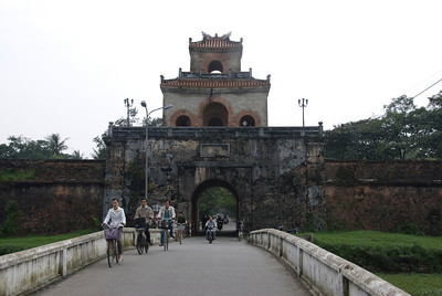Locals biking near the main Citadel gate - Hue, Vietnam