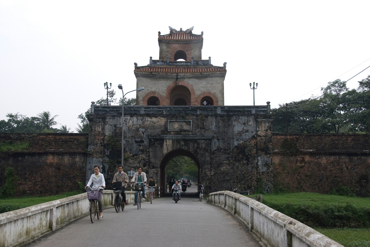 Locals biking near the main Citadel gate - Hue, Vietnam