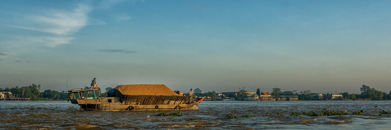 A boat in the morning sunshine on the Cổ Chiên River.
