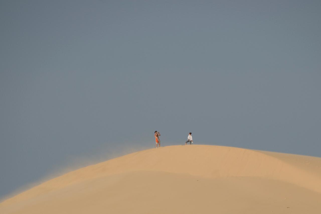 Tourists taking photos at the white sand dunes - Mui Ne, Vietnam