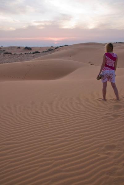 Woman walking barefoot on white sand dunes - Mui Ne, Vietnam