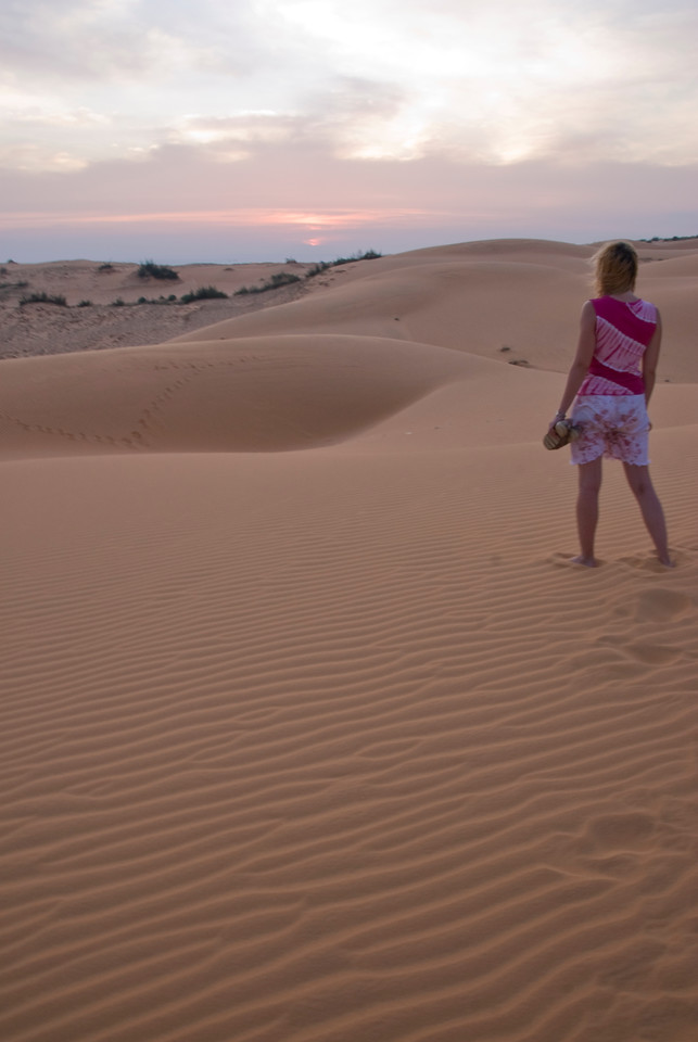 Woman walking barefoot on white sand dunes - Mui Ne, Vietnam