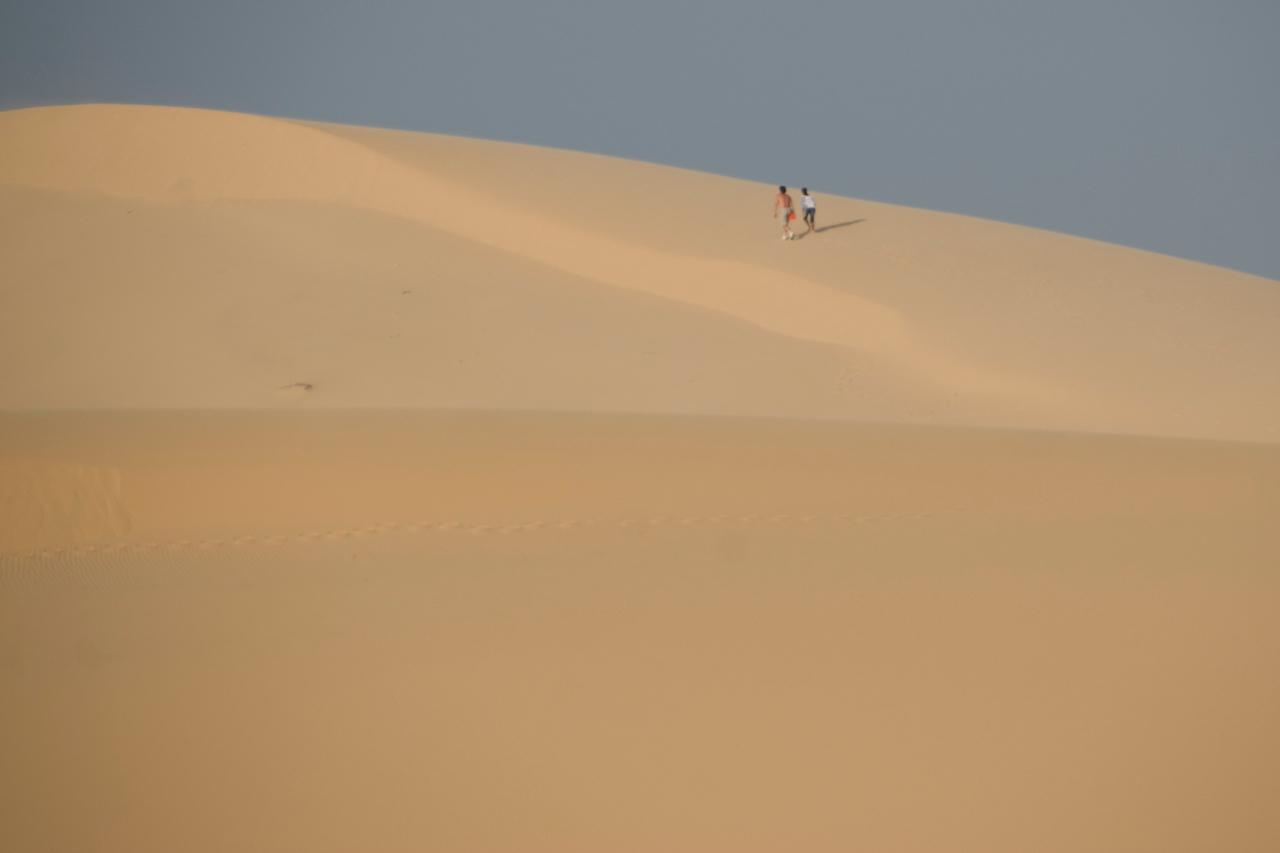 Tourists walking over white sand dunes - Mui Ne, Vietnam