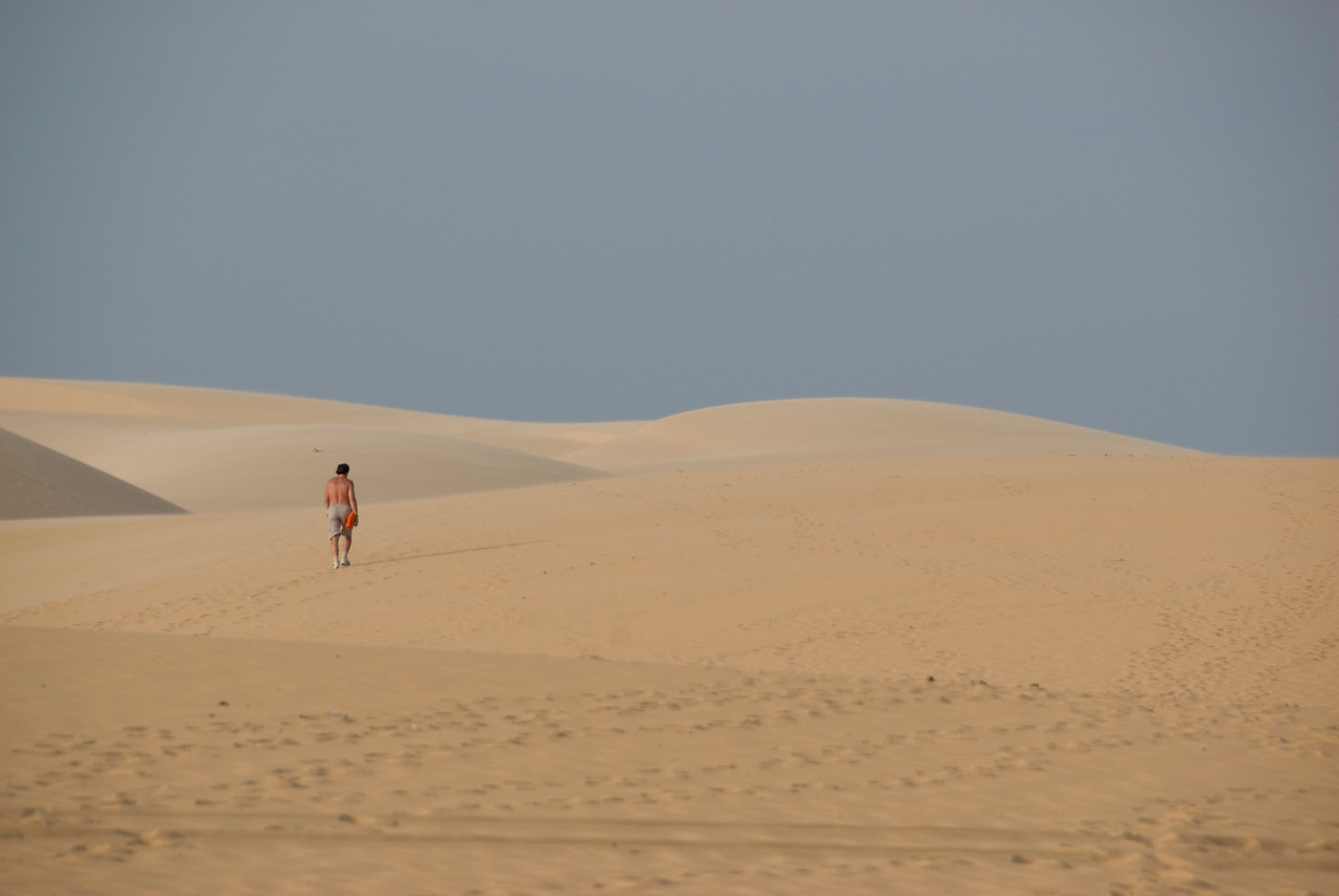 Man walking on white sand dunes - Mui Ne, Vietnam