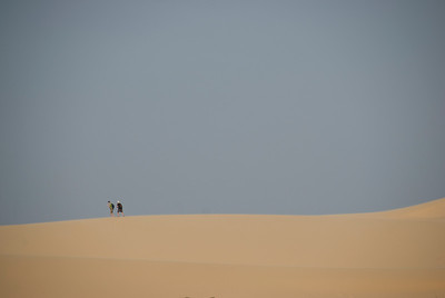 Two men walking over the white sand dunes - Mui Ne, Vietnam