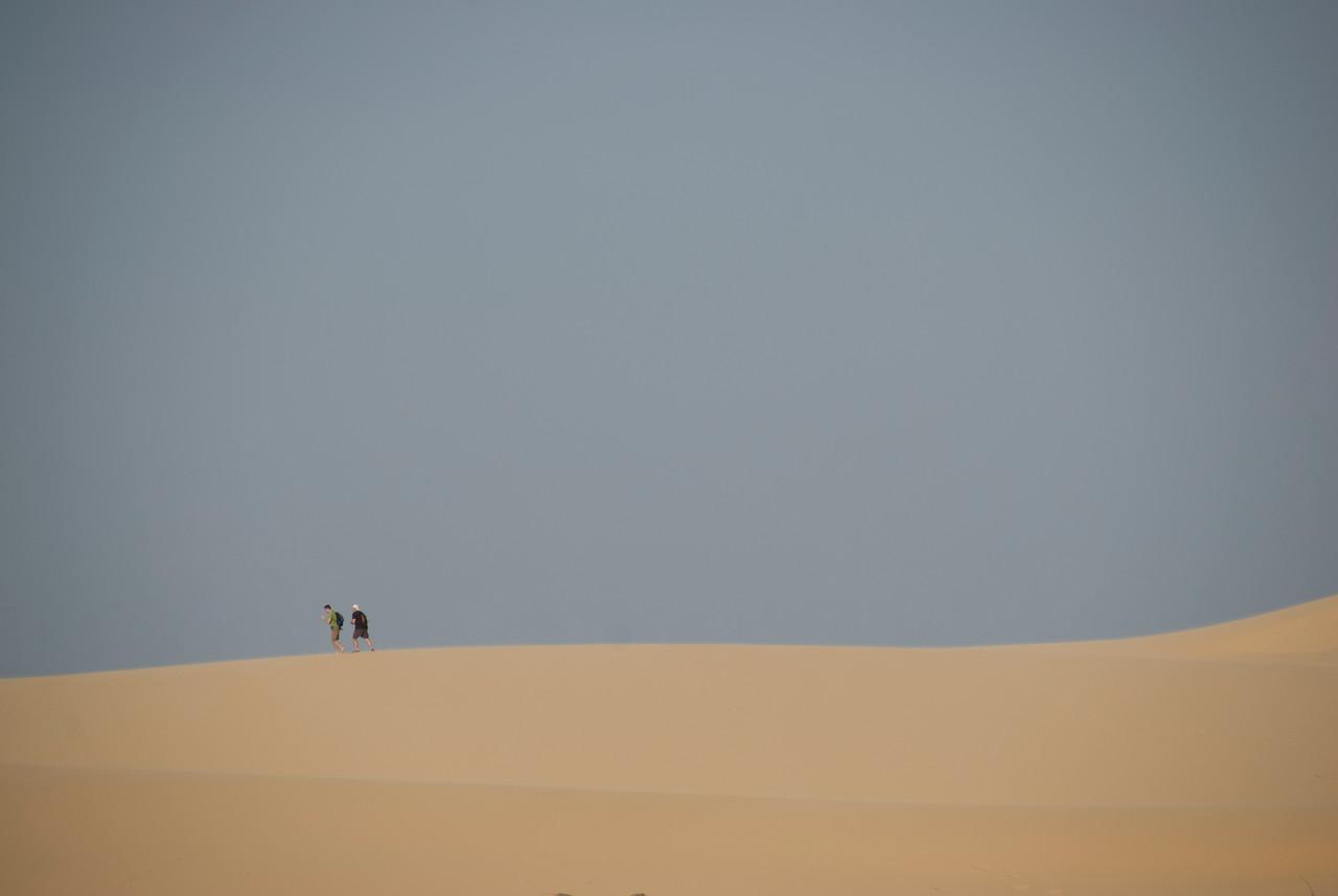 Two men walking over the white sand dunes - Mui Ne, Vietnam