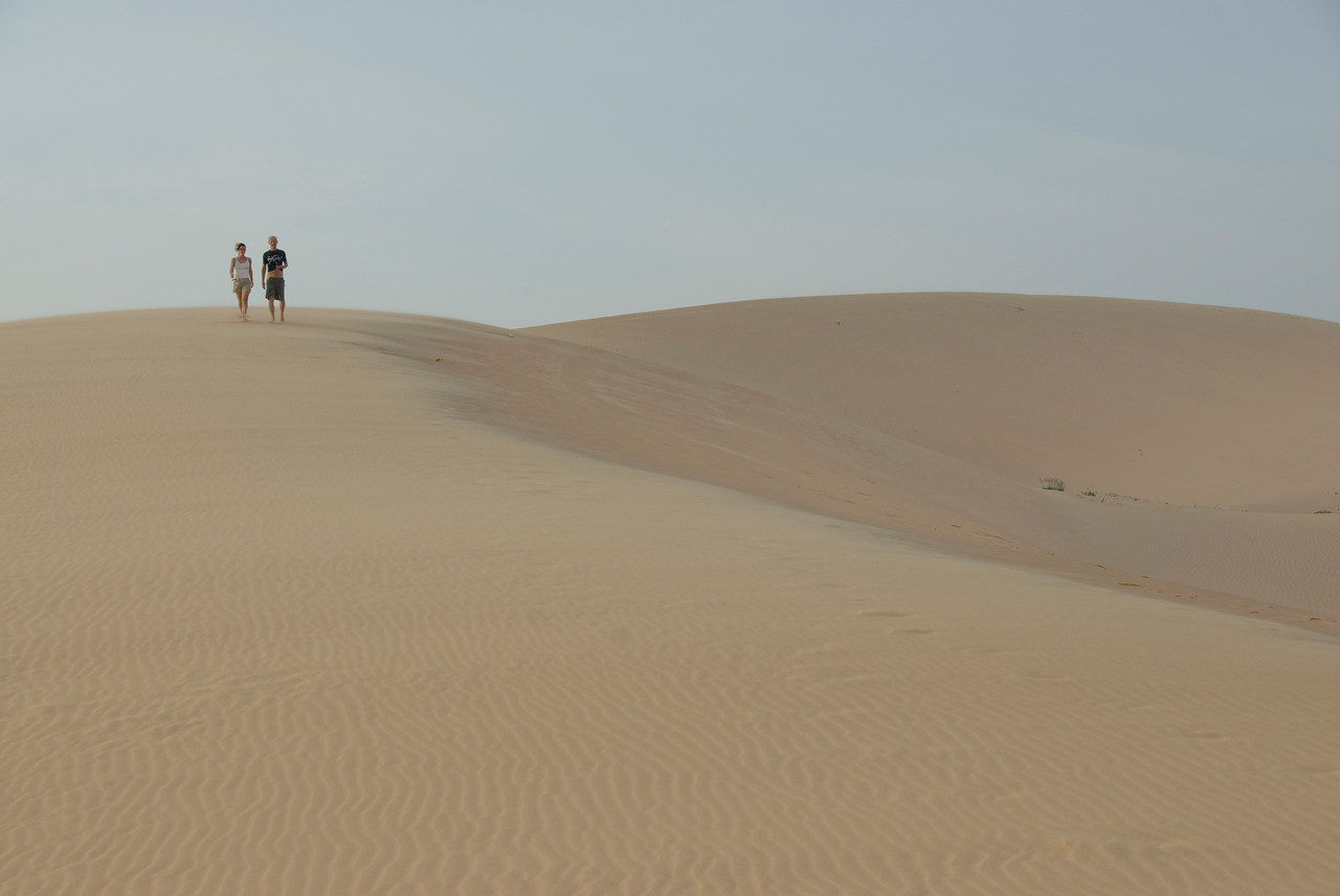 Couple takes a stroll at the white sand dunes - Mui Ne, Vietnam