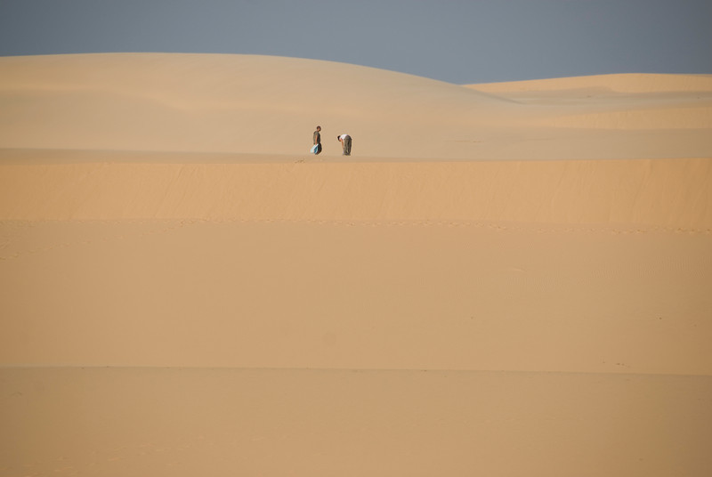 Tourists amidst expansive white sand dunes - Mui Ne, Vietnam