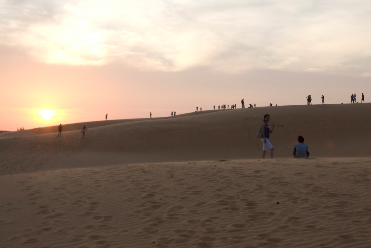Tourists at the white sand dunes during sunset - Mui Ne, Vietnam