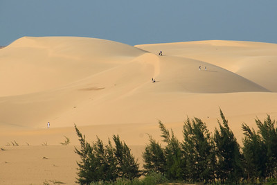 Tourists walking above the white sand dunes - Mui Ne, Vietnam