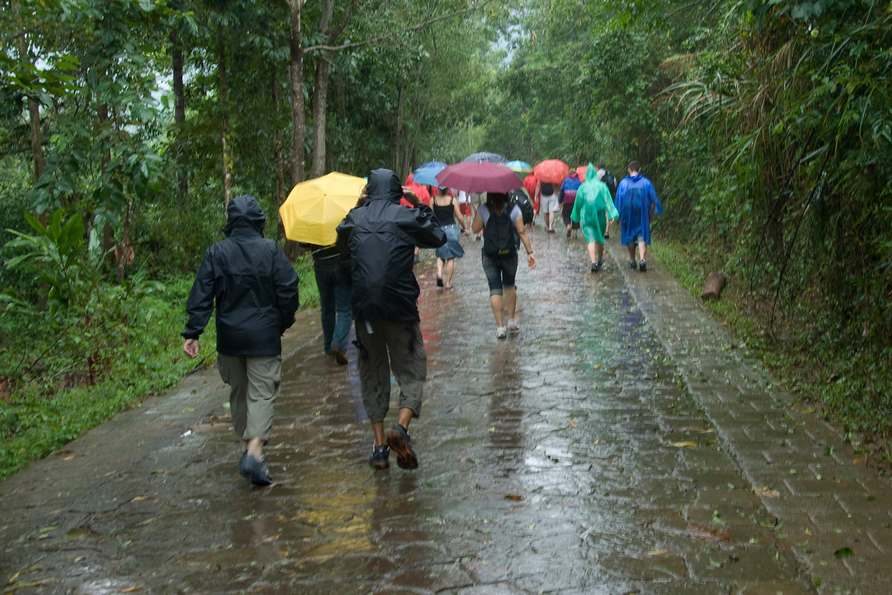 Tourists wearing rain gear while exploring My Son Sanctuary, Vietnam