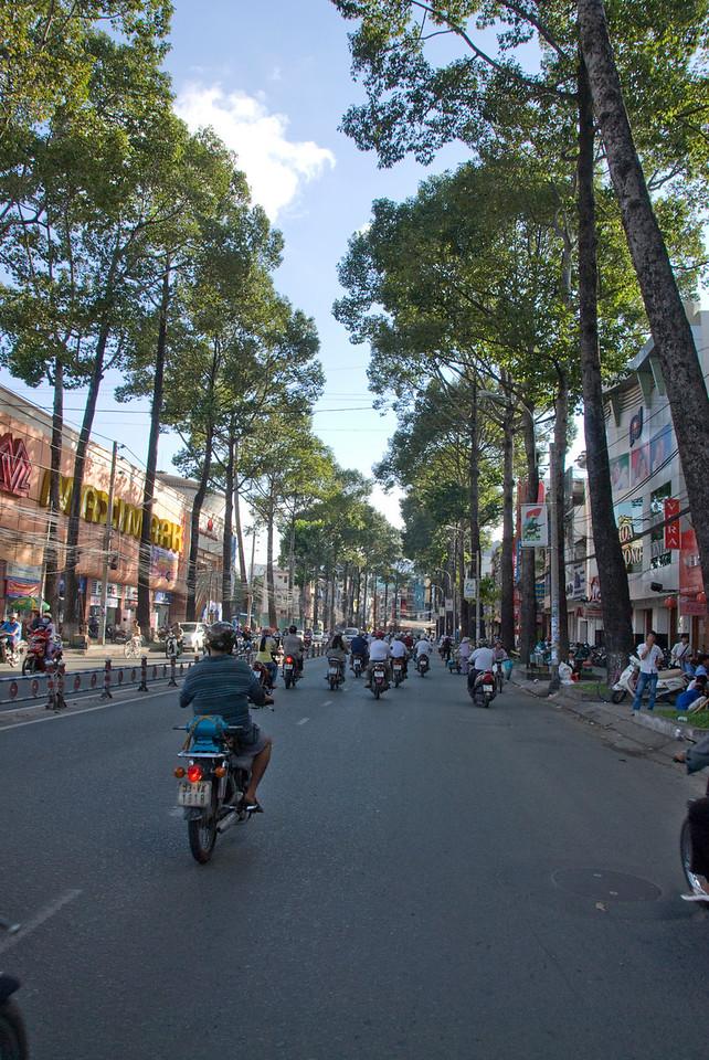 Motorists along tree-lined streets of Saigon, Vietnam