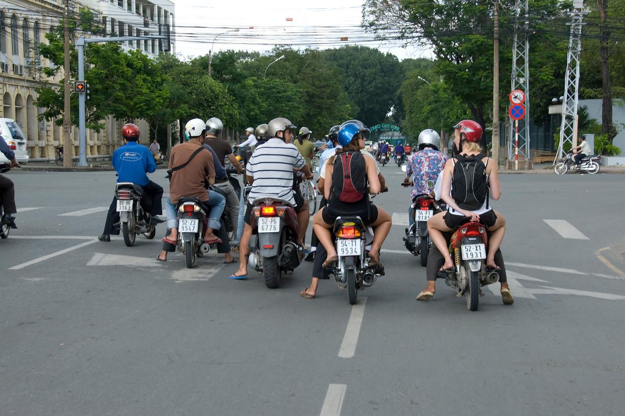 Motorcycle riders waiting on traffic stop sign - Saigon, Vietnam