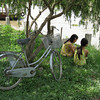 Two young girls having a quiet chat by a river in the Mekong Delta.