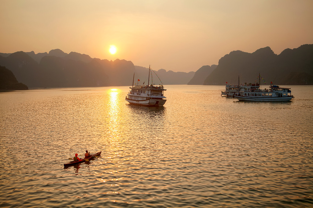 cat ba island sunset on tour boat with kayak and tour boats in foreground