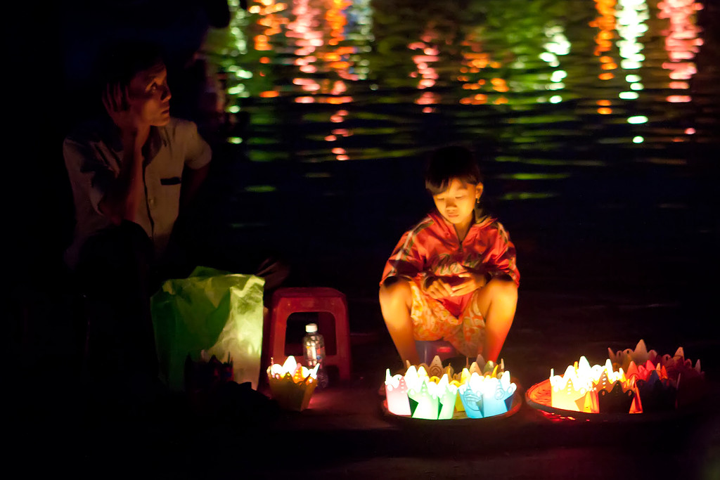 little girl and father selling lanterns at the hoi an full moon festival