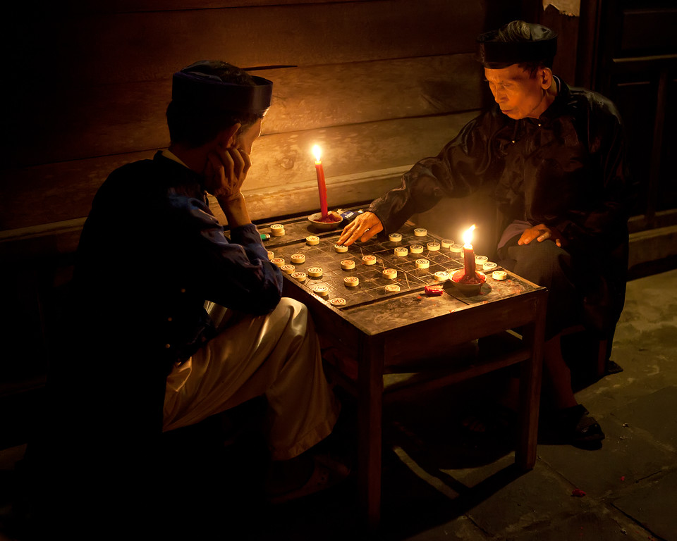 two men playing asian board game Xiangqi in traditional dress by candlelight