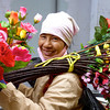 A woman in Hanoi poses while carrying a batch of fresh flowers to the market.
