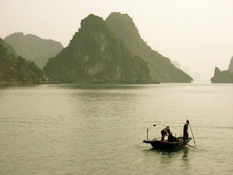 Fishermen coasting through Halong Bay waters.  Many fishermen still live in remote floating villages.