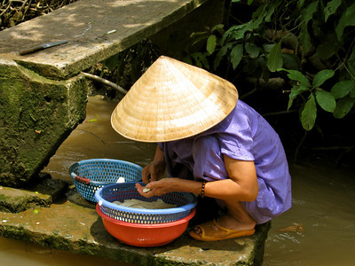 Preparing food along a canal in the Mekong Delta.