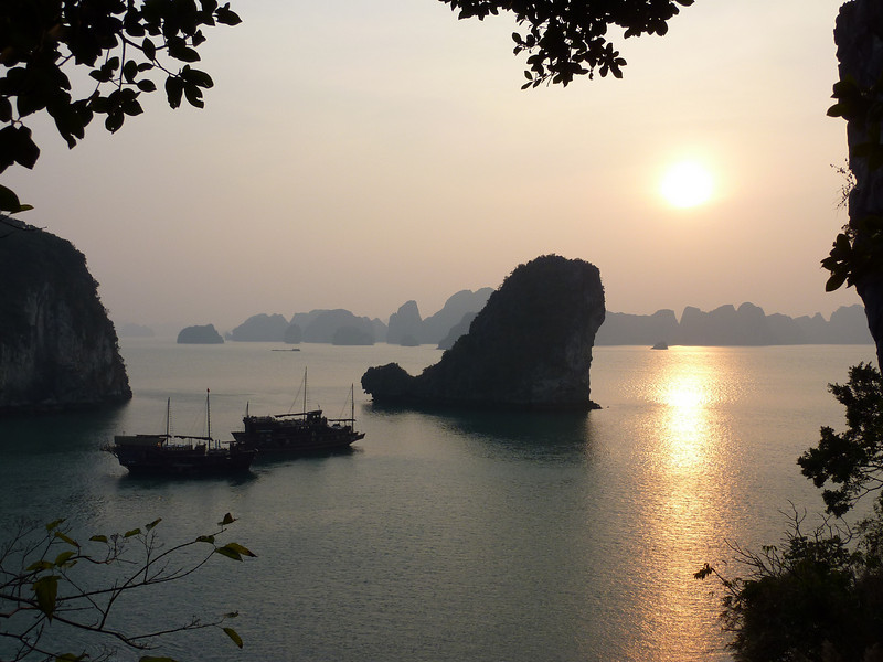 A sunset during a clear evening in Halong Bay, Vietnam.  Junk boats rest peacefully in the water.