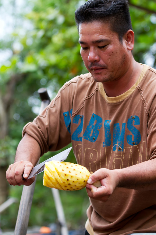 vietnamese asian man preparing pineapple in mekong delta