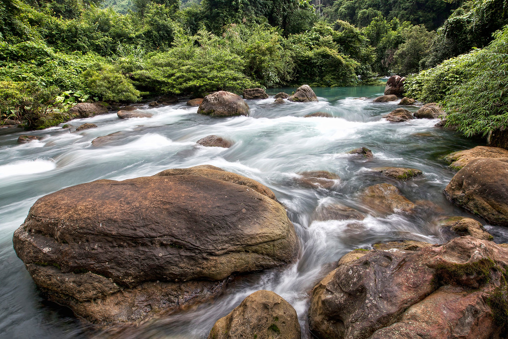 river rushing aroud a large boulder in phong nha ke bang national park vietnam