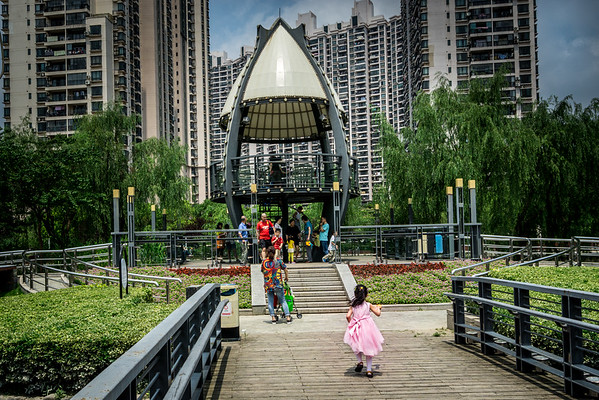 Girl in pink runs to her family during a Saturday afternoon outing at Suzhouhe Park in Shanghai