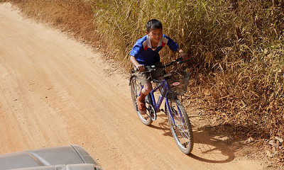 Children biking alongside the pickup truck heading to Akha Ama coffee village near Chiang Mai, Thailand.