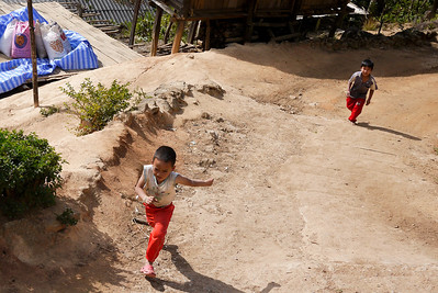 Excited kids run behind the truck when we arrive at the Akha Ama coffee village near Chiang Mai, Thailand.
