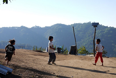Children play in the dusk at the Akha Ama coffee village near Chiang Mai, Thailand.