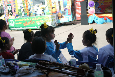 Young Thai dancers pass the time, Bo Sang Umbrella Festival, Chiang Mai, Thailand