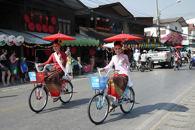 Pageant as the girls ride bikes through the town, Bo Sang Umbrella Festival, Chiang Mai, Thailand
