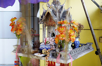 A colorful spirit house at a small outdoor coffee shop in Chiang Mai, Thailand protects the establishment and visitors.