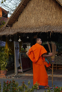 Monk takes a break from sweeping the temple clean at sunset, Chaing Mai, Thailand