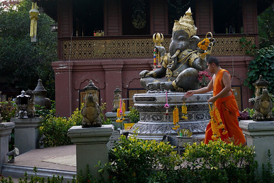 A monk at the Silver Temple in Chiang Mai, Thailand takes the offerings off of Ganesh for the evening.