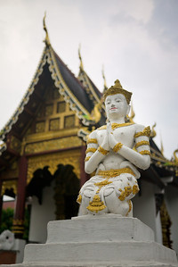 A statue guards on the wall surrounding a wat in Chiang Mai, Thailand.