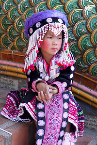 A pensive look from a young girl who performs and dresses in traditionally hilltribe clothes for the tourists in Chiang Mai, Thailand