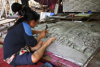 A silver-smith carves the silver reliefs at Wat Srisuphan Chiang Mai, Thailand