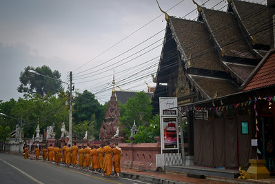 Monks walk the streets of Chiang Mai, Thailand for morning alms