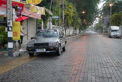 A rainy day at dawn is hte perfect time to wash a car on the emptry streets of Chiang Mai, Thailand