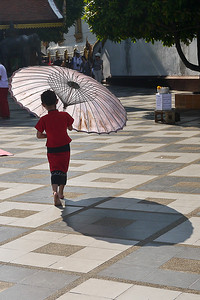 A young girl at Doi Suthep temple plays with a umbrella at sunset in Chiang Mai, Thailand