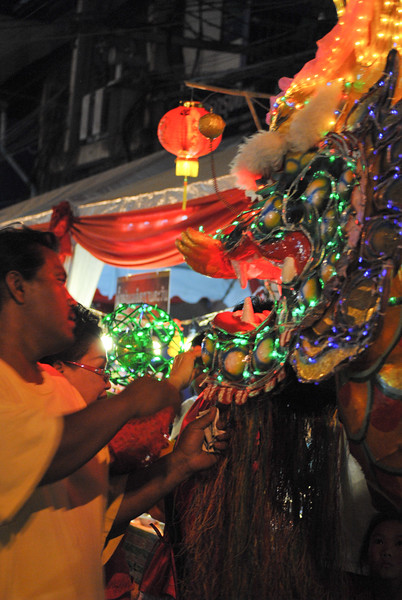 Feeding the dragon for good luck in the New Year Chinese NY festivities in Chiang Mai, Thailand.