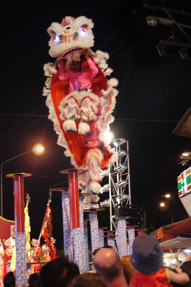 Dragon performers leap between posts at the Chinese New Year festivities in Chiang Mai, Thailand.