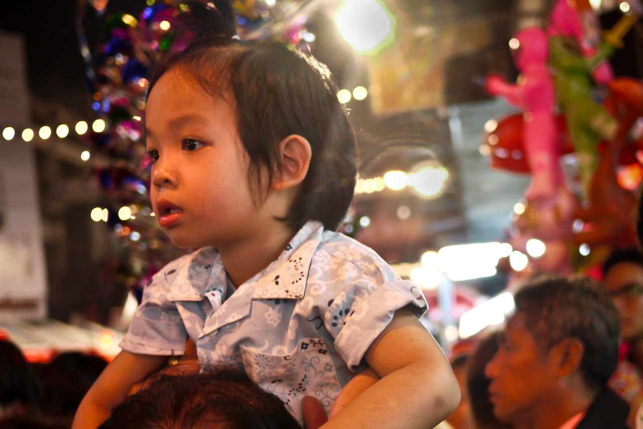 Little girl on her dad's shoulders at the Chinese New Year festivities in Chiang Mai, Thailand.